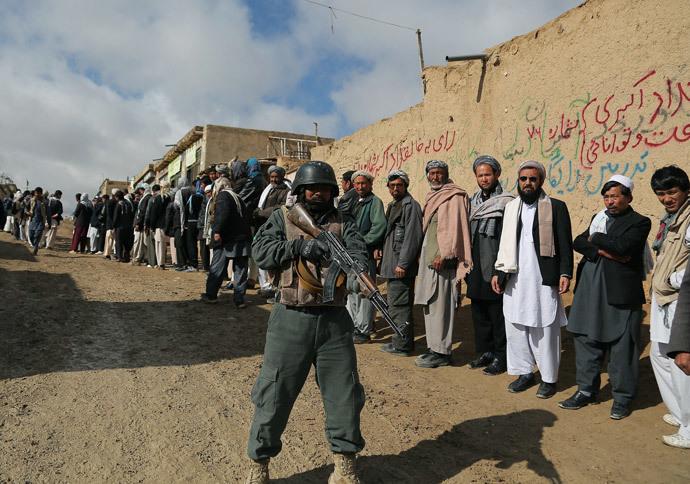 Um policial afegão vigia eleitores afegãos fazendo fila para votar em um posto de votação local em Ghazni em 5 de abril de 2014. (AFP / Rahmatullah Alizadah)