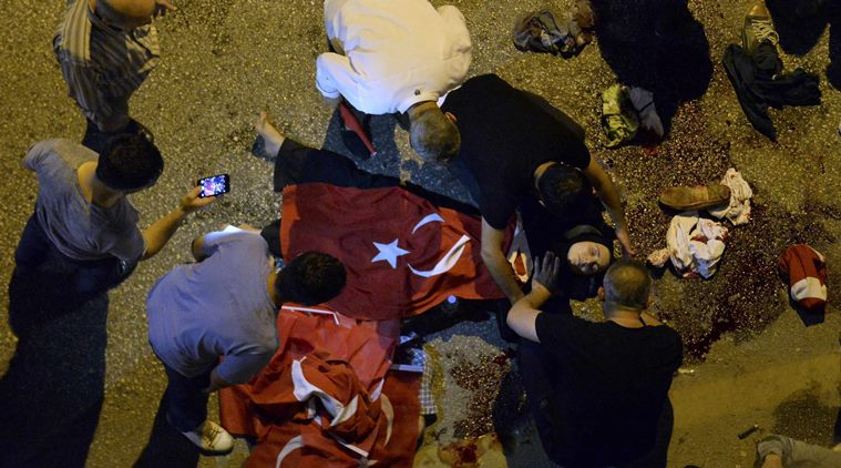 An injured woman draped in a Turkish flag is checked by others near military headquarters in Ankara
